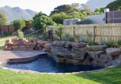 A pool that is designed to merge into the landscape seamlessly. Distinct waterfalls add a lovely dynamic of musical waterfalls. A natural stone fireplace and wind barrier has also been created by our hard landscaping.